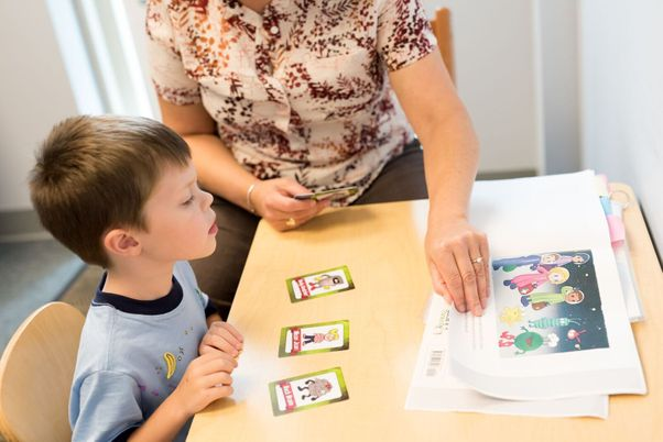 A child and therapist reviewing worksheets representing executive function disorder treatment offered by South Shore Therapies in Southern MA